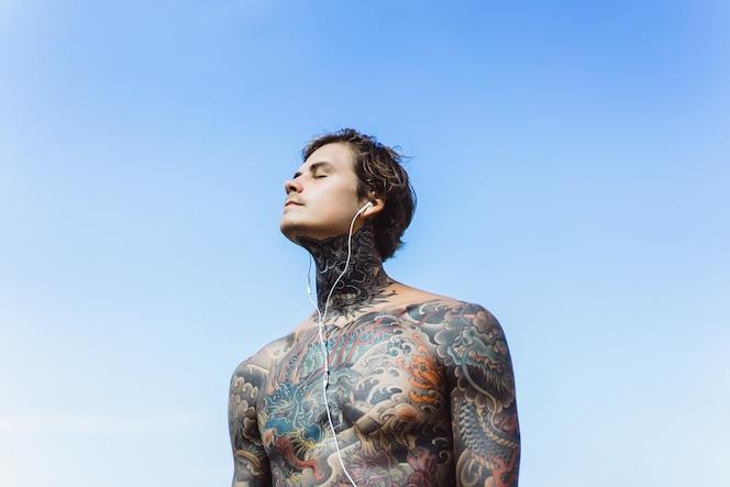 Hombre tatuado con auriculares contra el cielo azul en el océano