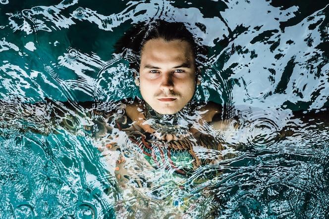 Hombre tatuado en la piscina bajo la lluvia.