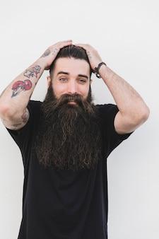 Hombre tatuado joven sorprendido que se opone a la superficie blanca