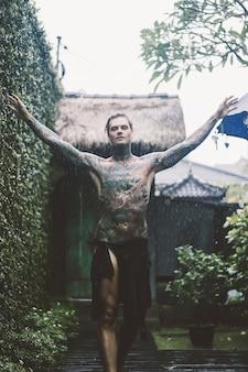 Hombre tatuado posando bajo la lluvia