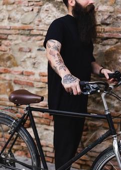 Hombre tatuado que sostiene la bicicleta contra la pared de ladrillo resistida