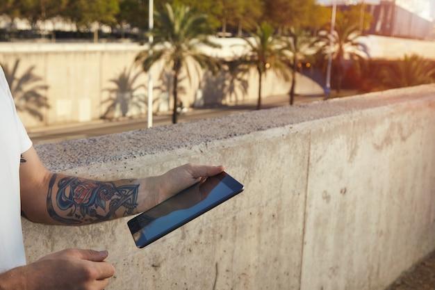 Hombre tatuado sosteniendo una tableta negra de pie junto a un muro de hormigón gris en el paisaje de la ciudad con palmeras