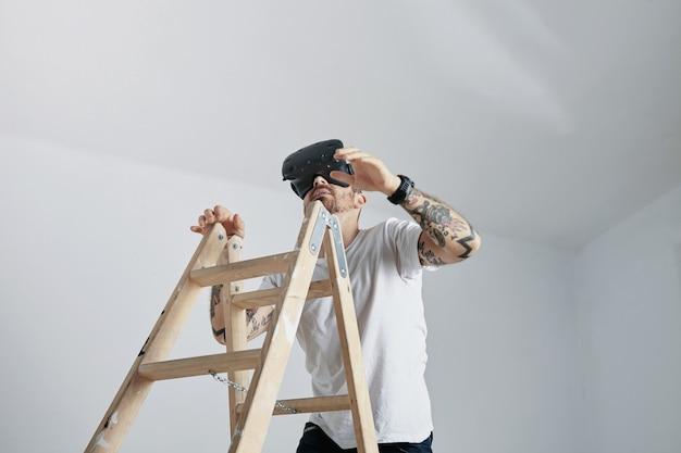 Un hombre con tatuajes en camiseta blanca en blanco y auriculares vr subiendo una escalera en una habitación con paredes blancas