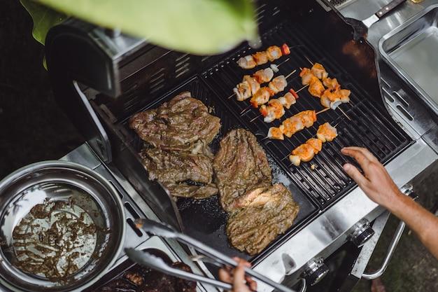 Un hombre en tatuajes hace barbacoa parrilla carne al aire libre.