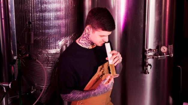 Hombre con tatuajes produciendo cerveza artesana