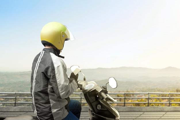 Hombre de taxi de motocicleta asiática revisando orden en su teléfono