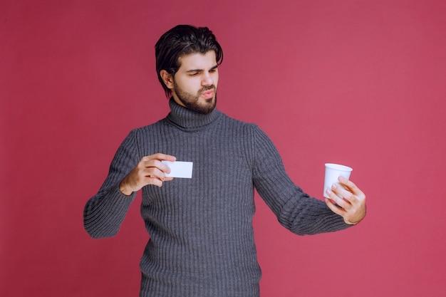 Hombre con una taza de café mostrando su factura o tarjeta de visita.