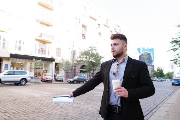 Un hombre con una taza de café en sus manos se para junto a la carretera y toma un taxi.