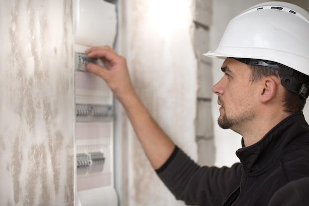 Hombre, un técnico eléctrico que trabaja en una centralita con fusibles. instalación y conexión de equipos eléctricos.