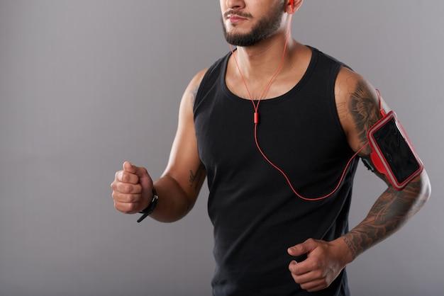 Hombre con teléfono en brazalete corriendo