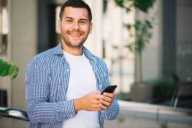 Hombre con teléfono inteligente cerca de la escalera