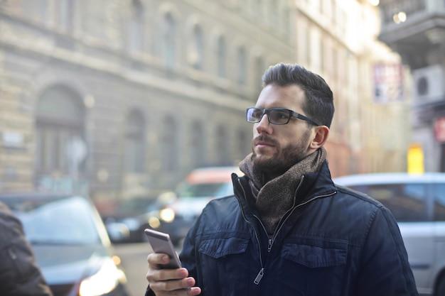 Hombre con un teléfono inteligente en invierno