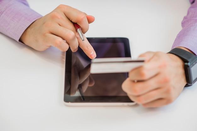 Hombre con teléfono inteligente y tarjeta de crédito. compra en línea.