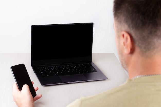 Un hombre con un teléfono en la mano se sienta frente a una computadora portátil con una maqueta negra en el monitor, el concepto de trabajo de oficina, trabajo remoto, marketing, capacitación, coaching