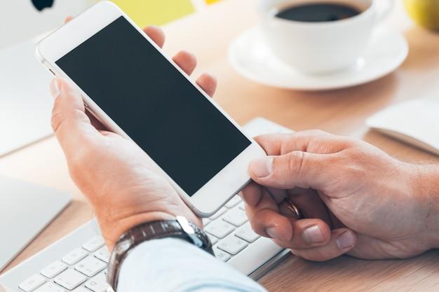 Hombre con teléfono móvil inteligente, manos de hombre de negocios con teléfono celular en el escritorio de la oficina