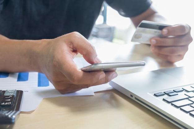 Un hombre con teléfono móvil y tarjeta de crédito en la computadora portátil para las compras en línea