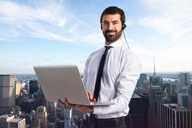 Hombre de telemarketer guapo con la computadora portátil en fondo unfocused