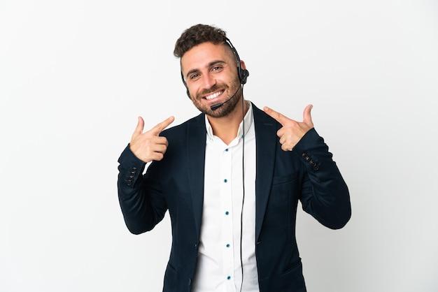 Hombre de telemarketer que trabaja con un auricular aislado en blanco dando un pulgar hacia arriba gesto