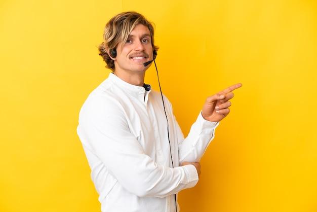 Hombre de telemarketer que trabaja con un auricular aislado en la pared amarilla que señala el dedo hacia el lado