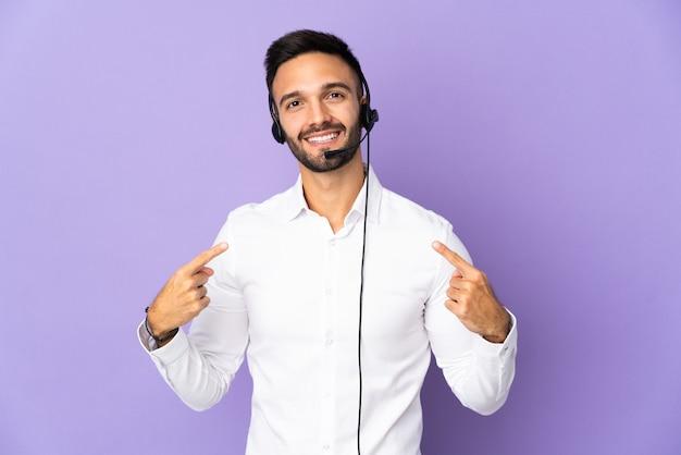 Hombre de telemarketer que trabaja con un auricular aislado sobre fondo púrpura dando un pulgar hacia arriba gesto
