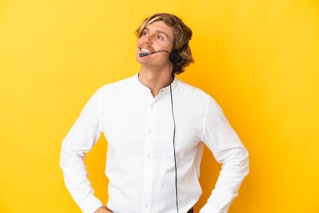 Hombre de telemercadeo que trabaja con un auricular aislado en la pared amarilla pensando en una idea mientras mira hacia arriba