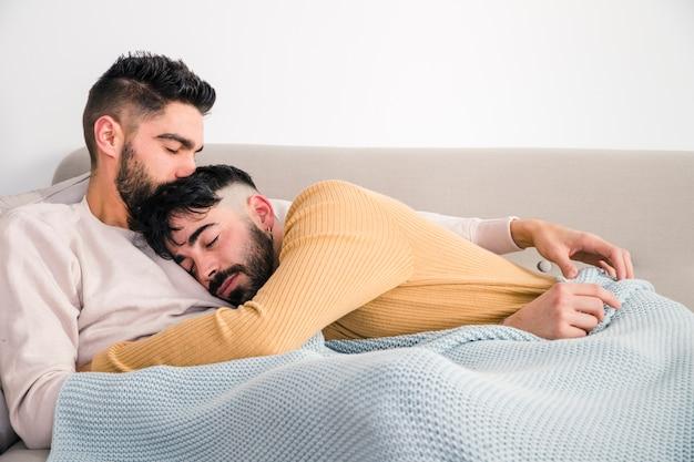 Hombre tendido en el pecho de su novio sobre el sofá contra la pared blanca