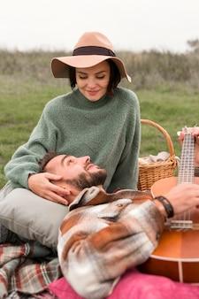Hombre tendido en el regazo de la novia y tocando la guitarra