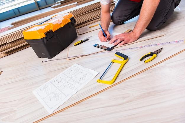 Hombre tendiendo pisos laminados en construcción