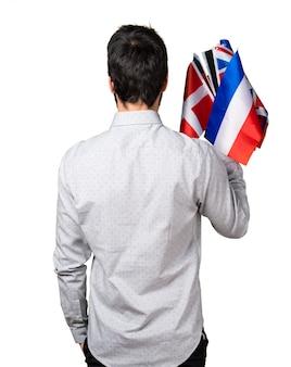 Hombre, con, tenencia, muchos, banderas, espalda, posición