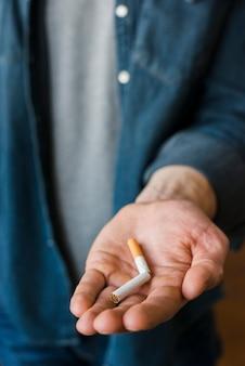 Un, hombre, tenencia, roto, cigarrillo, en, el suyo, mano
