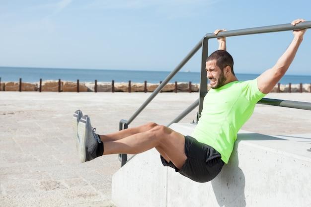 Hombre tenso haciendo suspensión de piernas en el mar