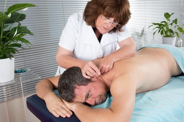 Hombre en una terapia de acupuntura en un centro de spa