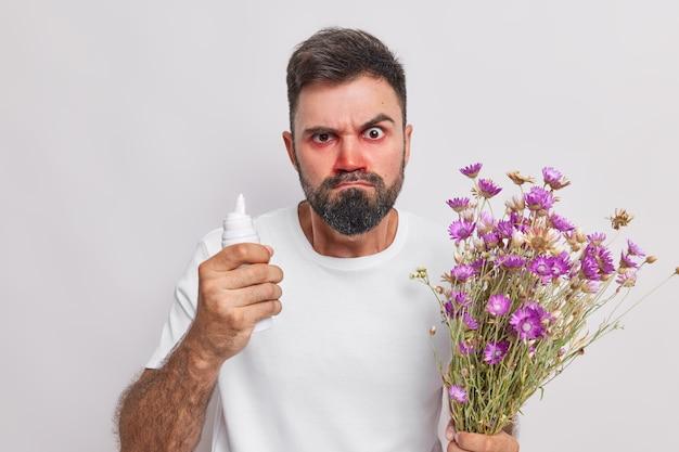 El hombre tiene aerosol para curar la reacción alérgica tiene alergia a las flores silvestres sufre de rinitis y los ojos llorosos posa en blanco