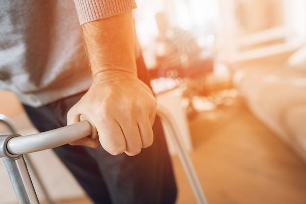 El hombre tiene un andador para adultos en un hogar de ancianos.