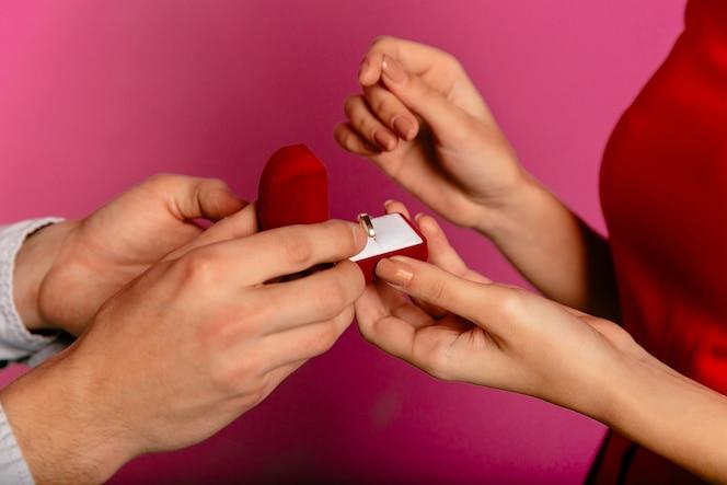 Hombre tiene caja de regalo con anillo de compromiso, va a hacer una propuesta a su novia