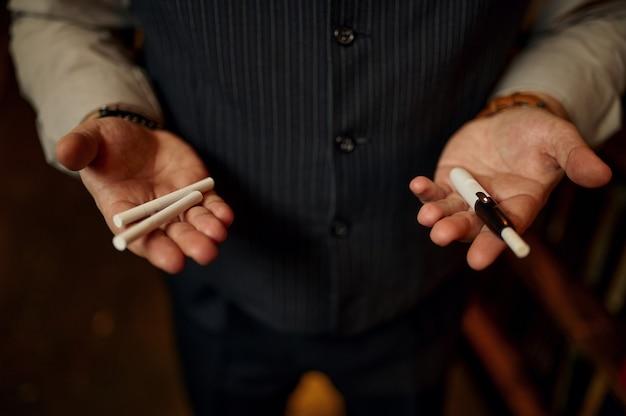 El hombre tiene cigarrillos y boquilla en sus manos, estantería y rico interior de oficina. cultura del tabaquismo, sabor específico. hábito de fumar