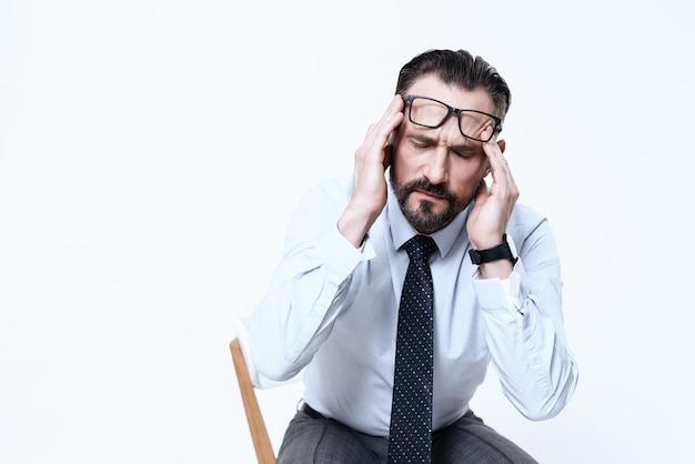Un hombre tiene dolor de cabeza. mantiene sus manos sobre su cabeza.