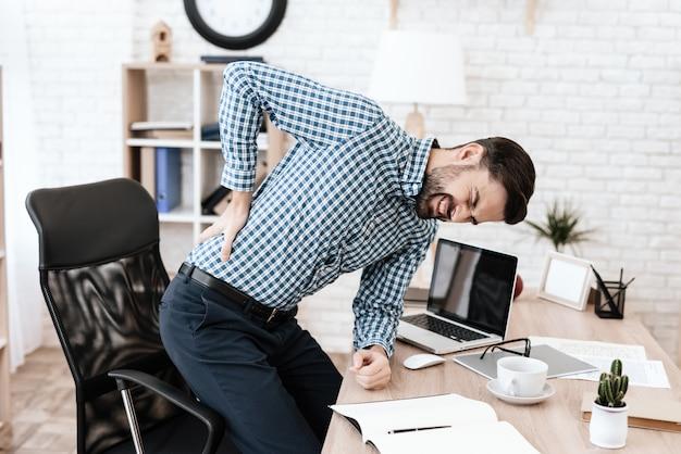 El hombre tiene dolor de espalda. él mantiene sus manos en la cintura.