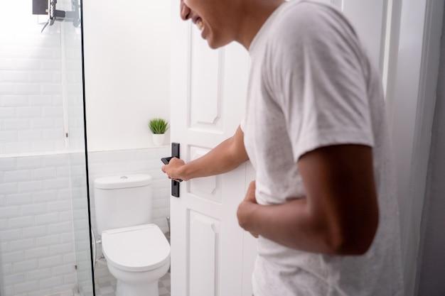 El hombre tiene dolor de estómago y va al baño
