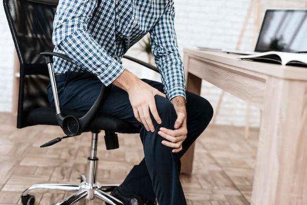 El hombre tiene un dolor en la pierna. él sostiene su mano el punto dolorido.