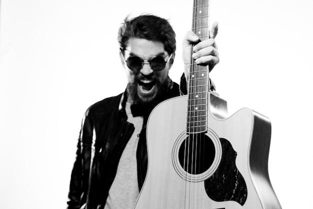 Un hombre tiene una guitarra en sus manos.
