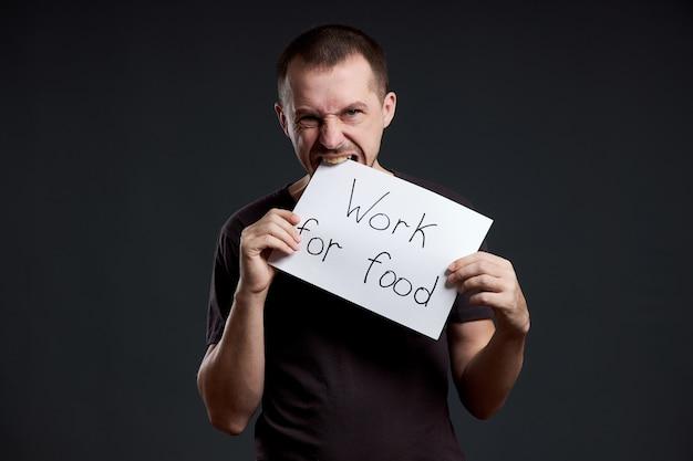 El hombre tiene una hoja de papel de cartel en sus manos con la inscripción trabajo por la comida.