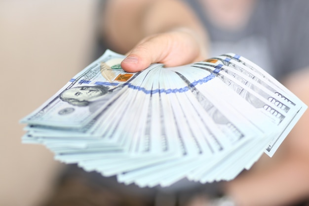 El hombre tiene en la mano un paquete grande y gordo de dinero estadounidense