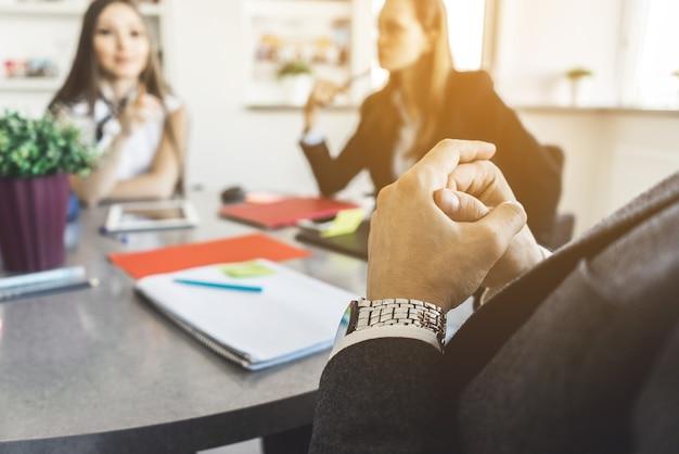 El hombre tiene de la mano, traje de traje, sentado en la reunión de negocios