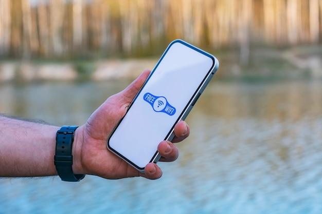 El hombre tiene un teléfono inteligente en la mano con un icono de wi-fi gratuito en la pantalla. teléfono en el fondo del bosque y el lago. acceso gratuito a internet en la naturaleza.