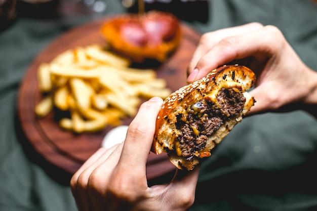 Hombre tiene vista lateral de hamburguesa de carne