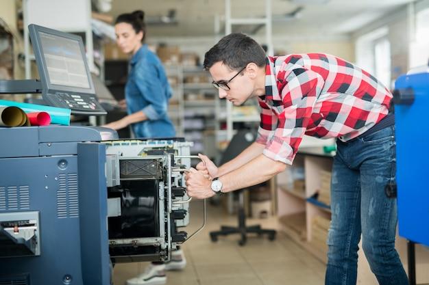Hombre en tipografía trabajando con impresora