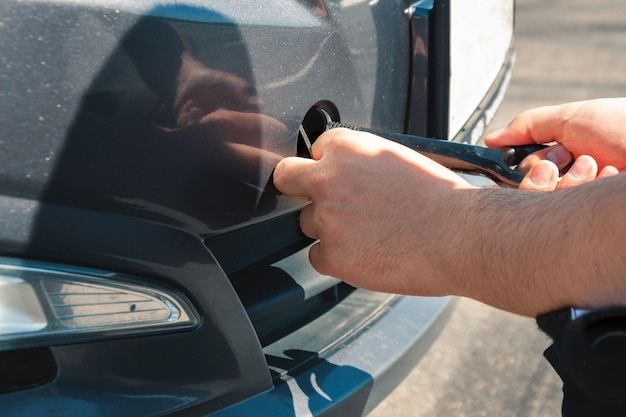 Un hombre tira un gancho para remolcar frente a un automóvil. desglose y remolque de automóviles.
