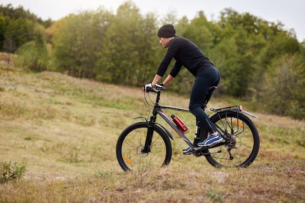 Hombre de tiro al aire libre montando bicicleta de montaña en una pradera, vestidos deportivos para hombre, traje negro y gorra, pasando tiempo libre de manera activa