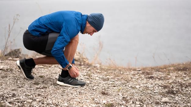 Hombre de tiro completo atando los cordones de sus zapatos en el sendero